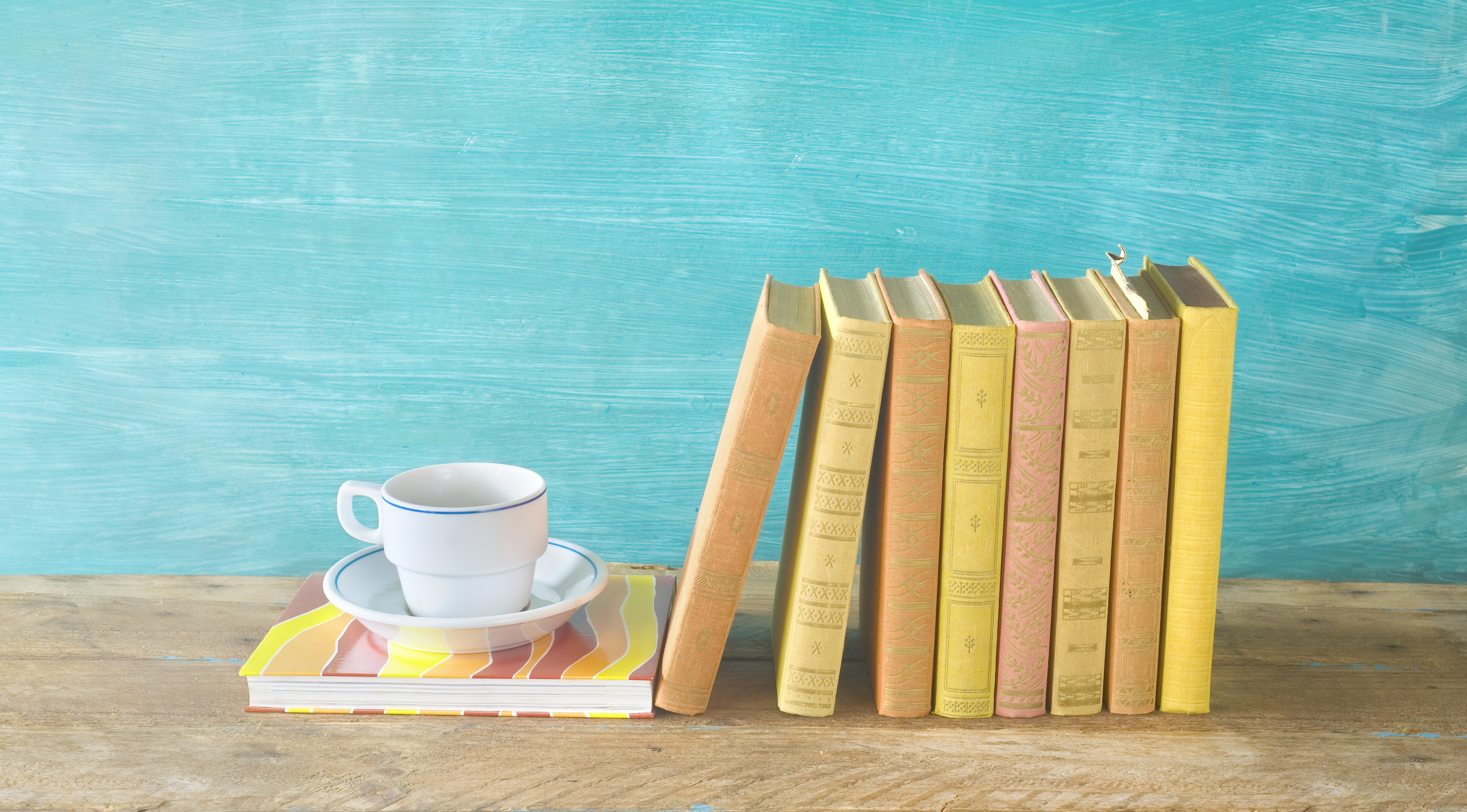 Row of old books and a cup of coffe on a rustic book shelf panorma,reading, literature,education